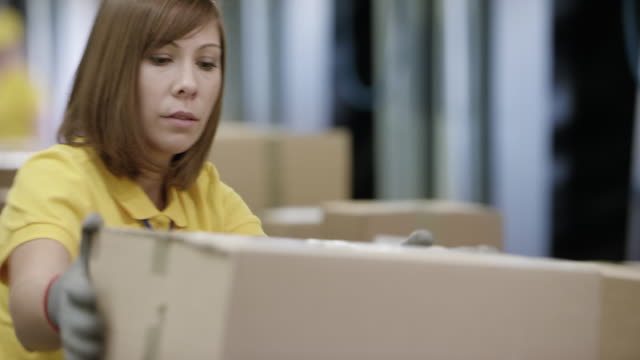 DS Female employee sorting packages on the conveyor belt in a warehouse