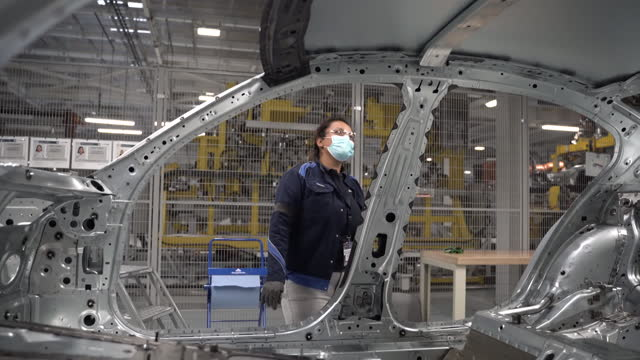 female employee wearing a protective mask working on the production floor of the bayerische motoren werke ag manufacturing facility in san luis... - car plant stock videos & royalty-free footage