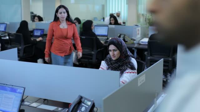 vídeos de stock, filmes e b-roll de female employees discuss work in an open plan office. male employees in traditional arab dress seen in the background. - países do golfo