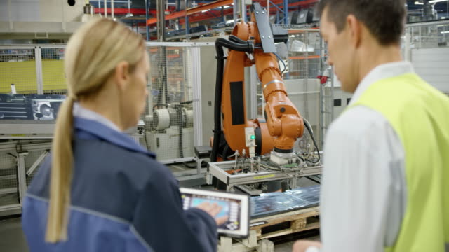 female engineer and representative of the company manufacturing robots inspecting the performance of the industrial robots - officina video stock e b–roll