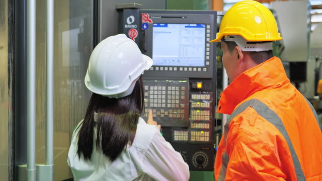 cnc機械のエンジニアと一緒に働く女性エンジニア見習い - 製造所点の映像素材/bロール