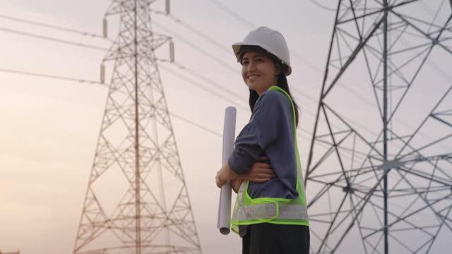 電柱の背景を持つ青写真を保持する建設現場の女性エンジニア請負業者 - 送電線点の映像素材/bロール