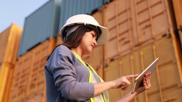 安全ヘルメットを身に着けている女性エンジニアの職長は、貨物コンテナの背景を持つデジタルタブレットを使用しています - 駅点の映像素材/bロール