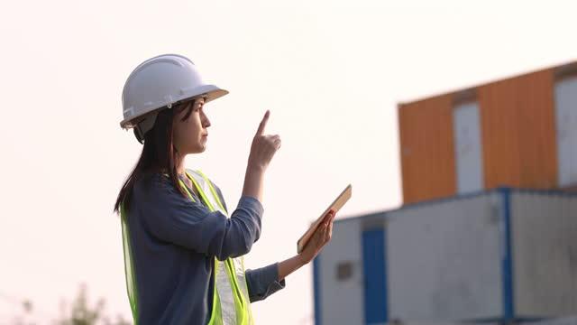 stockvideo's en b-roll-footage met vrouwelijke ingenieur voorman het dragen van veiligheidshelm gebruik digitale tablet met bakcontainer achtergrond - hoofddeksel