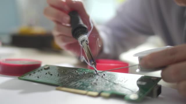 vidéos et rushes de fille d'ingénieur femelle réparant la carte de circuit avec le fer et le fil de soudure - ingénierie