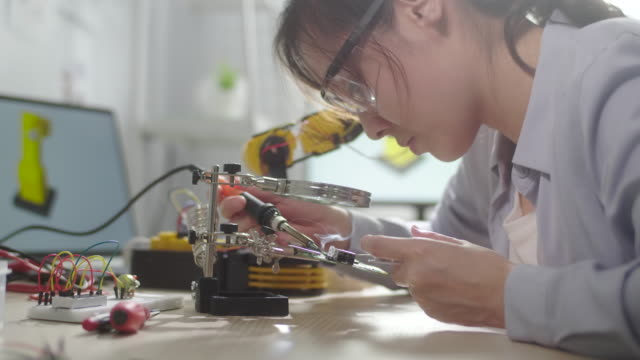 female engineer girl repairing the circuit board with soldering iron and wire - part of a series stock videos & royalty-free footage