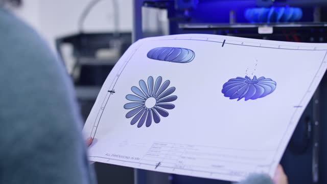vídeos de stock, filmes e b-roll de engenheira segurando uma folha impressa com o design de uma hélice de ventilador enquanto estava ao lado de uma impressora 3d - só uma mulher madura