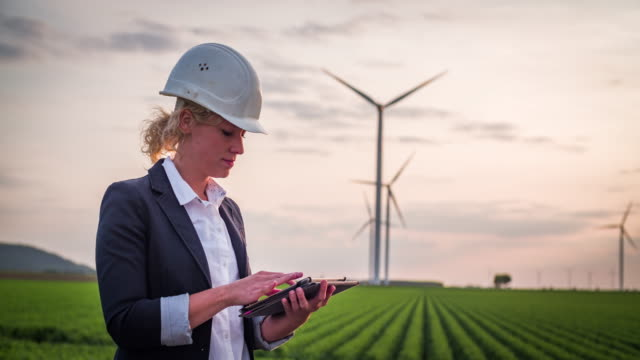 female engineer in front of wind turbines - women in stem - professione creativa video stock e b–roll