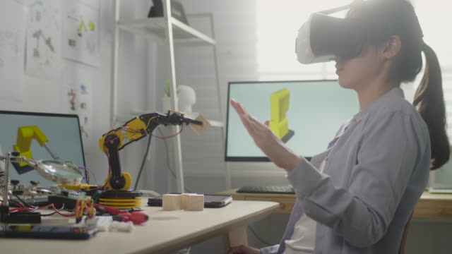 female engineer in virtual reality glasses moving hand for control robotic arm in office - engineering stock videos & royalty-free footage