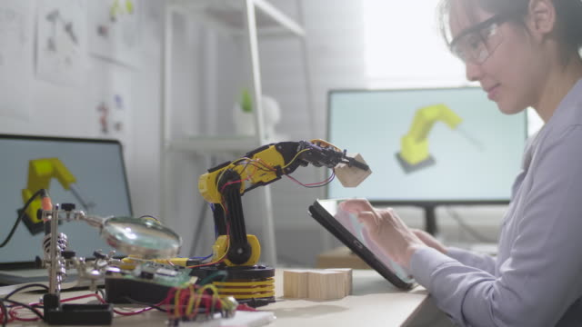 female engineer is working on innovative technology mechanical robot arm in his workshop,she using digital tablet controlling robotic arm by her hand - cyberspace stock videos & royalty-free footage