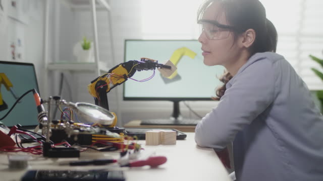 female engineer looking on on innovative technology mechanical robot arm in his workshop,she using digital tablet controlling robotic arm by her hand - studying stock videos & royalty-free footage