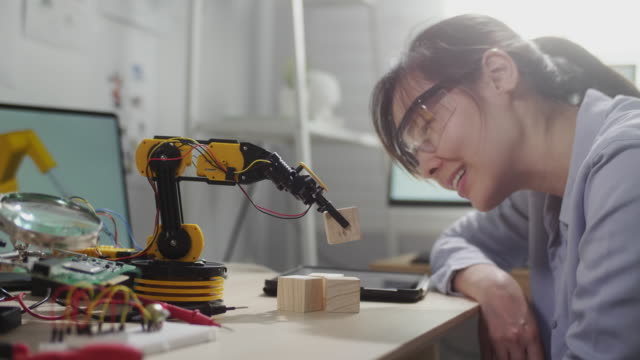female engineer looking on on innovative technology mechanical robot arm in his workshop,she using digital tablet controlling robotic arm by her hand - machine learning stock videos & royalty-free footage