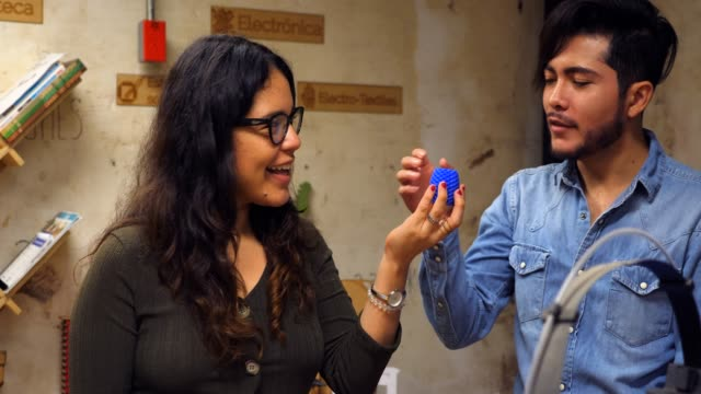 ms female engineer showing coworkers 3d printed piece for project - workshop stock videos & royalty-free footage