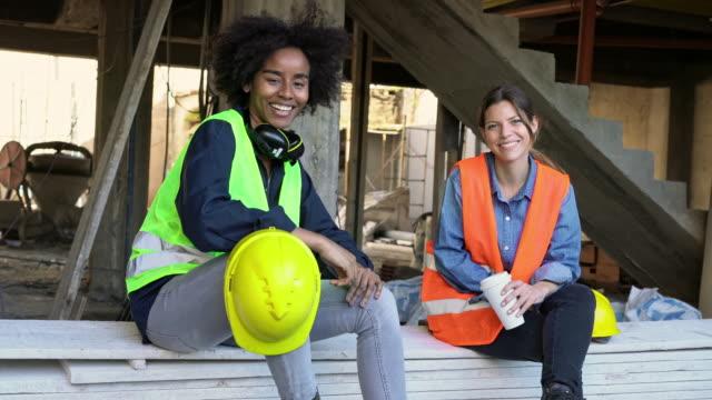 建設現場で板に座っている女性エンジニア - 使い捨てコップ点の映像素材/bロール