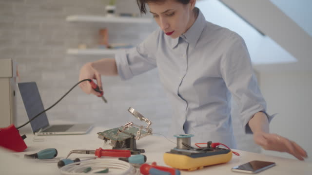 4K: Female Engineer Soldering a Circuit Board In Her Office.