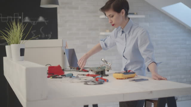 4K: Female Engineer Soldering a Circuit Board In Her Office.