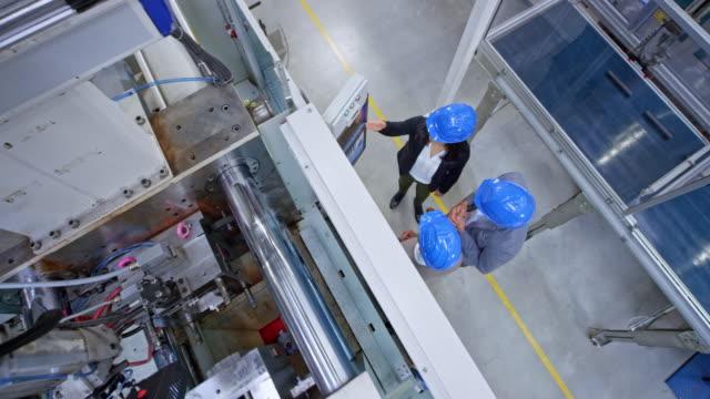 vidéos et rushes de cs ingénieur féminin restant dans l'usine et ayant une discussion avec les acheteurs par le panneau de commande de machine - crane construction machinery