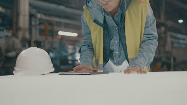 slo mo female engineer using a digital tablet in the factory - information medium stock videos & royalty-free footage