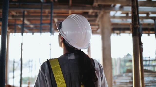 vídeos de stock, filmes e b-roll de engenheira feminina utilizando tablet digital em canteiro de obras para verificação de estrutura - capacete de trabalho