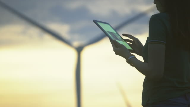 female engineer using tablet computer outdoors on wind turbines background. - energia rinnovabile video stock e b–roll