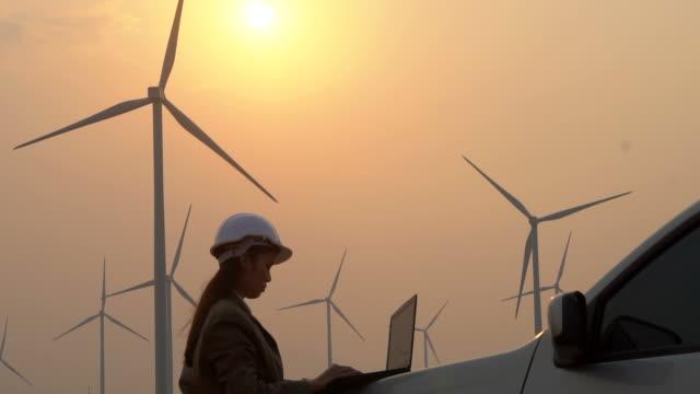 風力タービンの背景に屋外でタブレットコンピュータを使用して女性エンジニア。 - 整備員点の映像素材/bロール