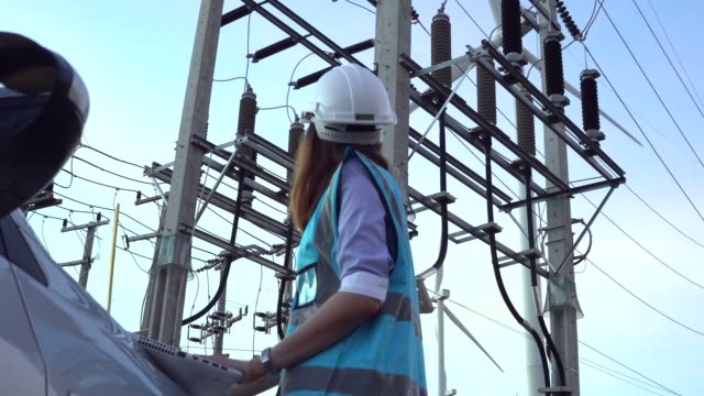 female engineer using tablet computer outdoors on wind turbines background. - maintenance worker stock videos & royalty-free footage
