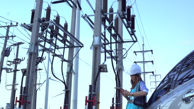 female engineer using tablet computer outdoors on wind turbines background. - addetto alla manutenzione video stock e b–roll