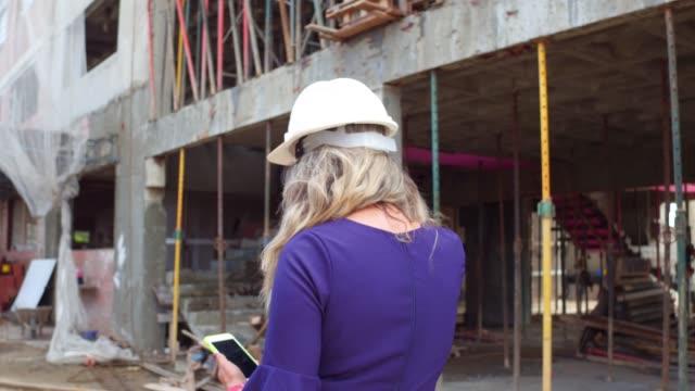 建設現場を歩いている女性エンジニア-トラッキングショット - 土木技師点の映像素材/bロール