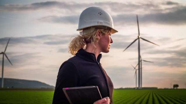 female engineer with digital tablet in front of wind turbines - environmental conservation stock videos & royalty-free footage