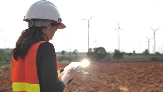 female engineer with digital tablet in front of wind turbines,women in stem - renewable energy stock videos & royalty-free footage