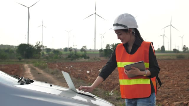 female engineer with laptop in front of wind turbines - alternative energy stock videos and b-roll footage