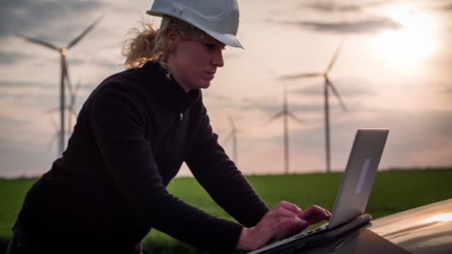 female engineer with laptop in front of wind turbines - women in stem - persona di sesso femminile video stock e b–roll