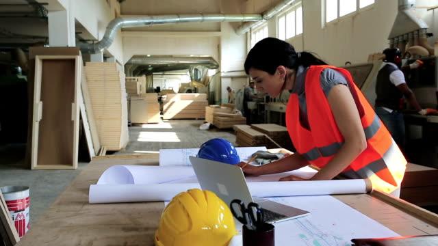 vidéos et rushes de ingénieur féminin travaillant sur un projet - ouvrier