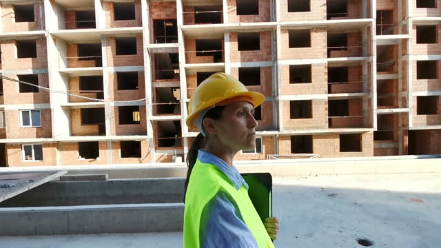 female engineer working on construction site with tablet, checking the work progress. - scaffolding stock videos & royalty-free footage