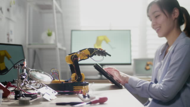 female engineer works with robot arm, she control robot arm with digital tablet - control stock videos & royalty-free footage