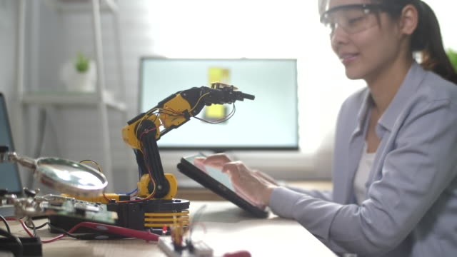 female engineer works with robot arm, she control robot arm with digital tablet - robotics stock videos & royalty-free footage