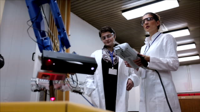 vídeos de stock e filmes b-roll de female engineers working with robotic arm in lab - engenheiro
