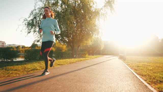 female enjoying running in park. - brown hair stock videos & royalty-free footage