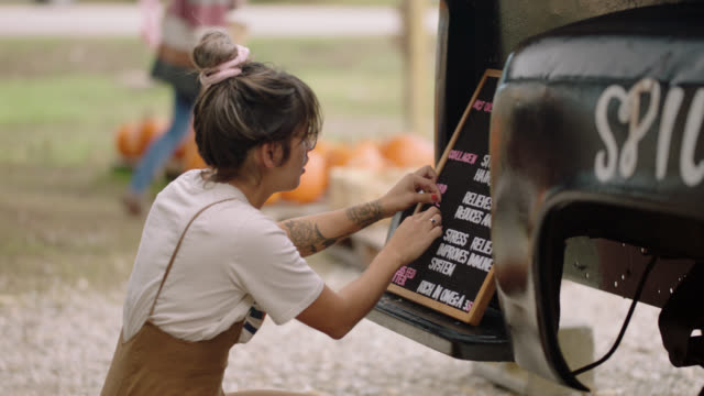 female entrepreneur arranges letters to a sign for her mobile coffee truck - booth stock videos & royalty-free footage