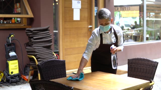 female entrepreneur cleaning and preparing her restaurant for reopening - entrepreneur stock videos & royalty-free footage