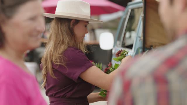 vídeos de stock, filmes e b-roll de female entrepreneur gathers flowers to make a bouquet at her mobile flower truck - rosa cor