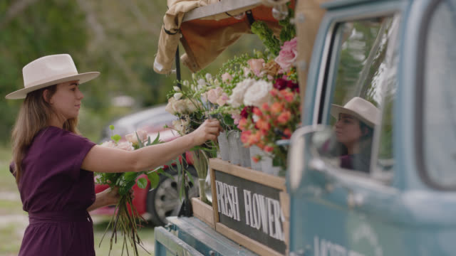 slo mo. female entrepreneur gathers flowers to make a bouquet at her mobile flower truck - bouquet stock videos & royalty-free footage