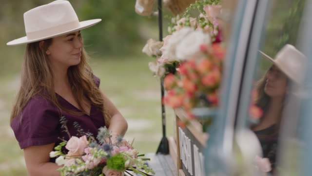slo mo. cu. female entrepreneur gathers flowers to make a bouquet at her mobile flower truck - flower shop stock videos & royalty-free footage
