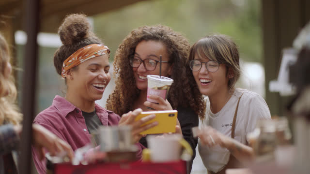 a female entrepreneur laughs at a phone together with customers at a mobile coffee truck - drinking stock videos & royalty-free footage