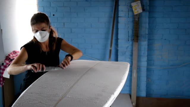 unternehmerin macht custom surfboards - surfbrett stock-videos und b-roll-filmmaterial