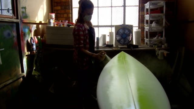 female entrepreneur making custom surfboards - spray painting stock videos & royalty-free footage