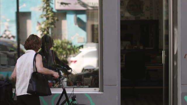 female entrepreneur parking bicycle and entering in design studio - purse stock videos & royalty-free footage
