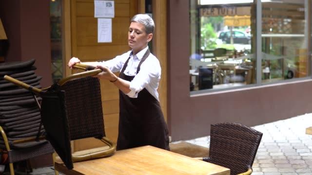 unternehmerin bereitet ihr restaurant auf die wiedereröffnung vor - sessel stock-videos und b-roll-filmmaterial