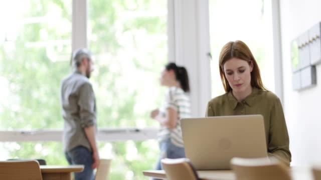 vídeos y material grabado en eventos de stock de female entrepreneur working on laptop with colleagues in the background - colega