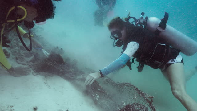 female environmental activists removing fishing nets from ocean floor - aqualung diving equipment stock videos & royalty-free footage